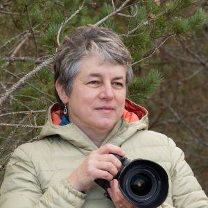Marie T Smith writer and wildlife photographer holding her Canon EOS digital camera