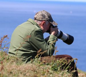 Stephen Smith - Smith Wild Photo practising photography, sat on the cliffs overlooking the Moray Firth