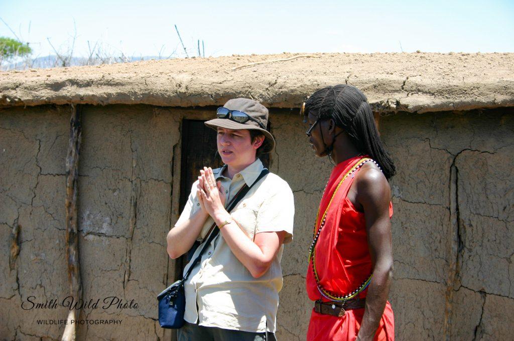 Woman and Masai warrior outside a Masai hut
